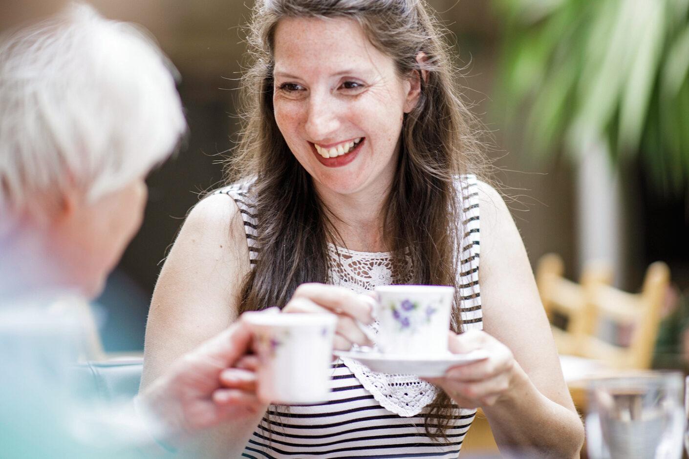 Foto: Junge Frau trinkt Kaffee, Betreuung im Rahmen der stationären Pflege der Diakonie Münster