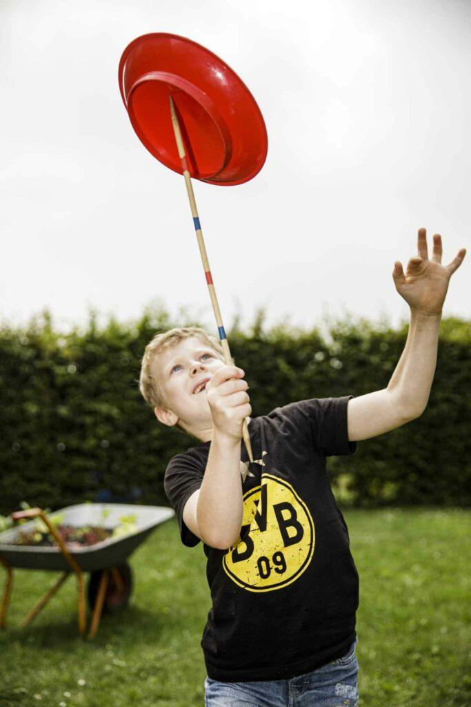 Fötö: Junge mit BVB-Shirt jongliert eine Teller auf einem Mikadostab; HTGs Diankonie Münster