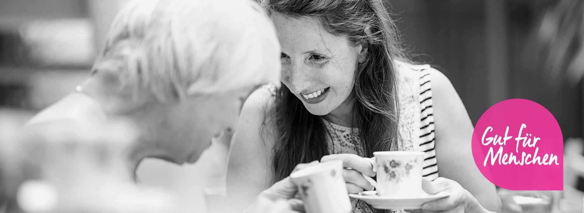 Foto: Lachende Altenpflegerin trinkt Kaffee mit älterer Dame