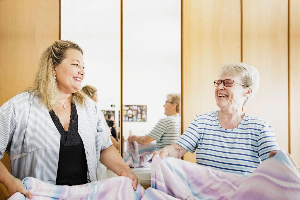 Foto: Foto: Ambulante Pflege - Pflegekraft unterstützt Seniorin beim Betten machen