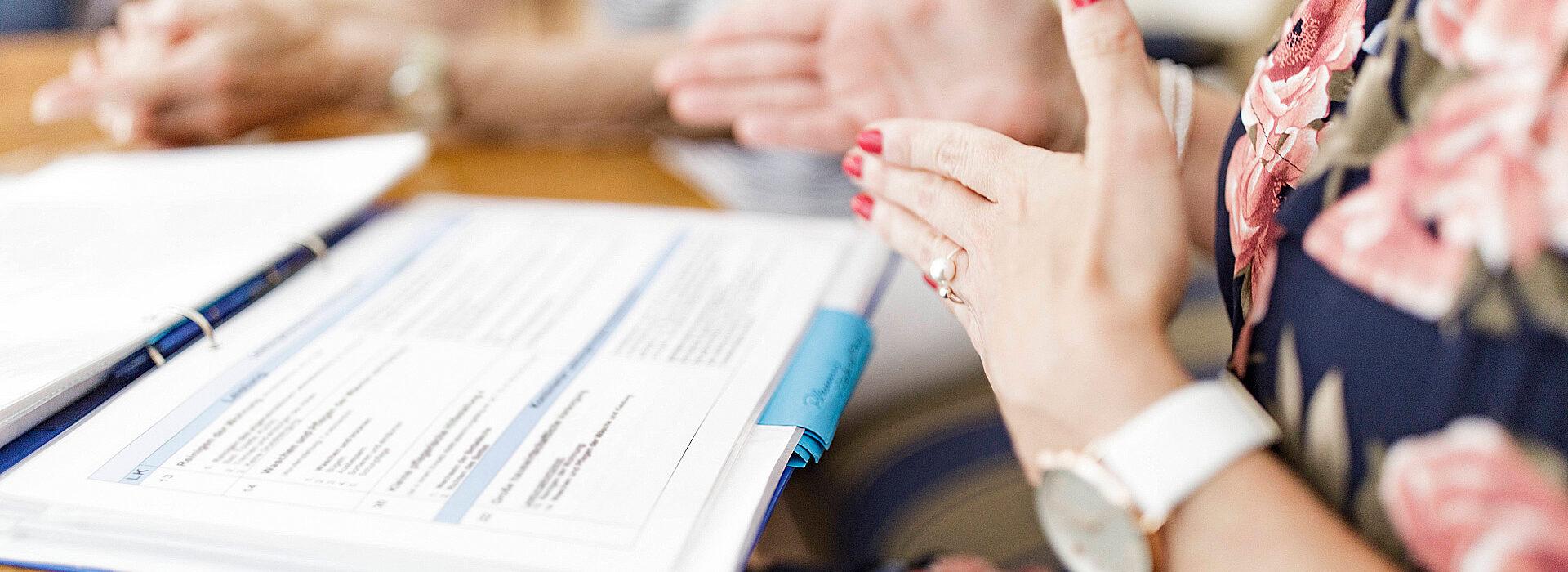 Foto: Gestikulierende Damenhände über einen Ordner - Schuldenberatung Diakonie Münster