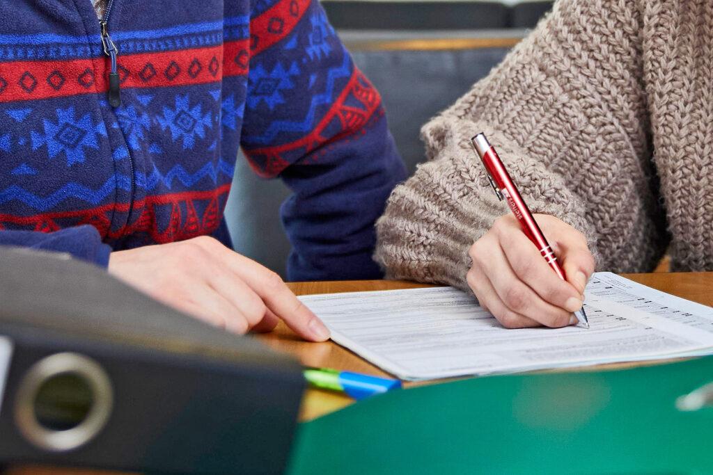 Foto: Betreuer unterstützt beim Ausfüllen von Formularen; Betreuungsverein der Diakonie Münster