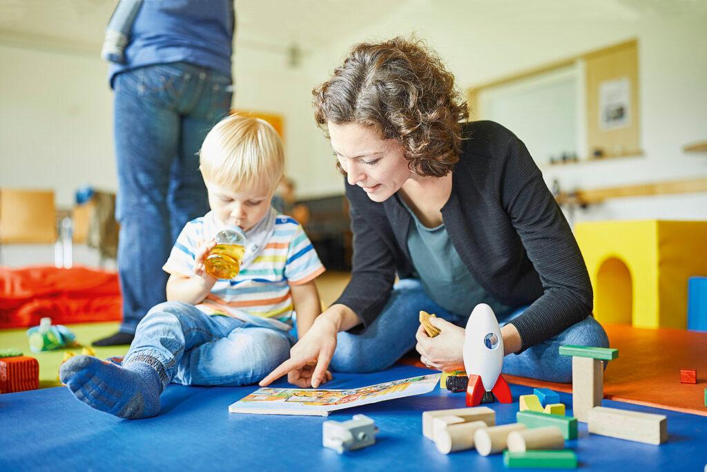 Foto: Familien- und Erziehungsberatung - Junge Frau und Kind schauen sich ein Bilderbuch an