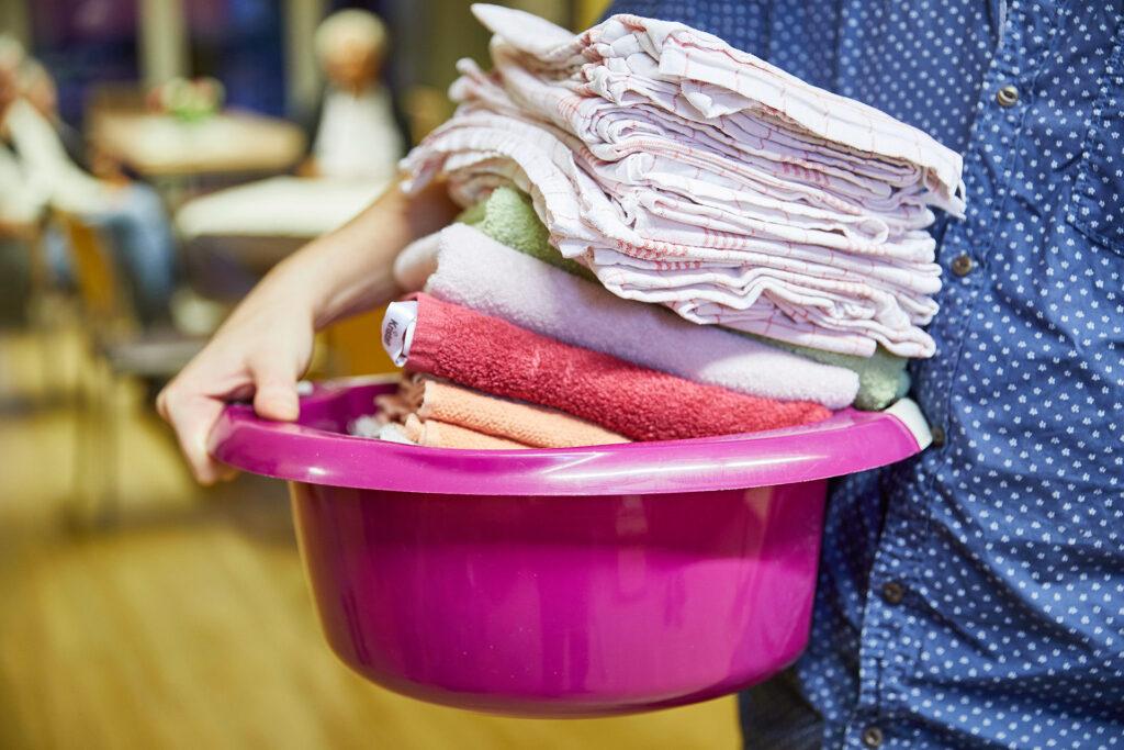 Foto: Schüssel mit Handtücher wird getragen; Hauswirtschaftliche Versorgung ambulant der Diakonie Münster