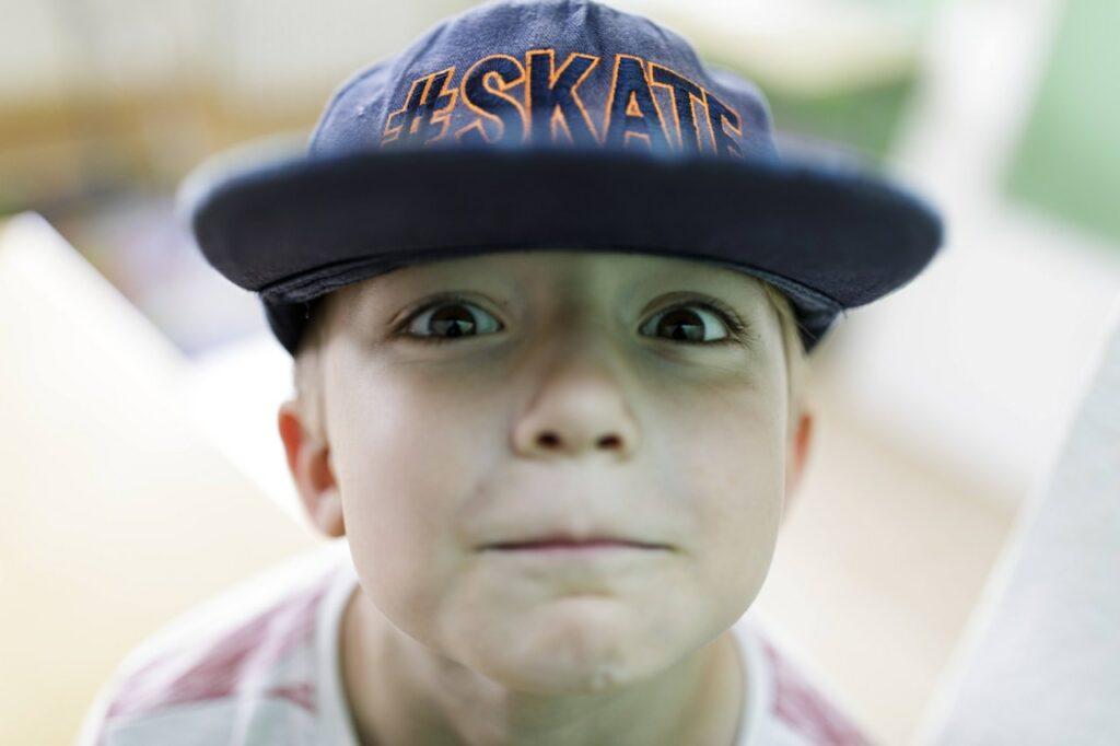 Foto: Kindergesicht mit Cap ganz nah am Objektiv