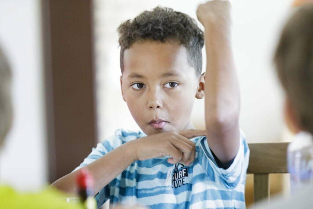 Foto: Junge zeigt auf seinen Oberarmmuske HTG West, Diakonie Münster