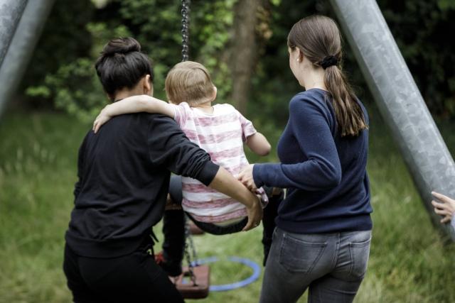 Foto: Zwei Betreuer tragen ein Kind zur Schaukel; Bereich Kinder, Jugend und Familie der Diakonie Münster