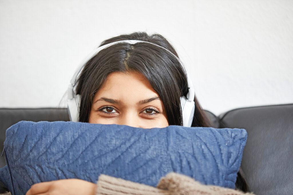 Foto: Junge Frau mit Kopfhörern hält ein Kissen - sozialpädagogisch betreutes Wohnen