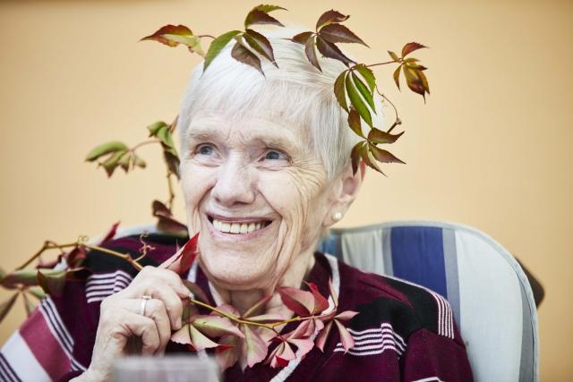 Foto: Ältere, sitzende Dame, die sich einen Strauch heranzieht