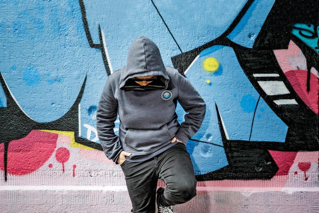 Foto: Jugendlicher mit Hoodie vor Grafittiwand
