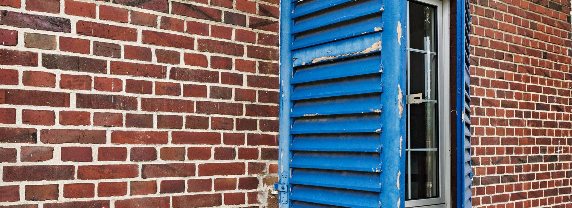 Foto: Klinkerwand mit halboffenen, blauen Fensterläden, Suchberatung der Diakonie Münster