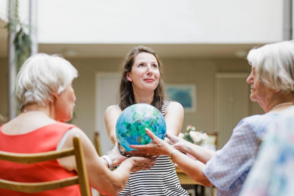 Foto: Pflegefachkraft aktiviert ältere Pflegebedürftige, Tagespflege der Diakonie Münster