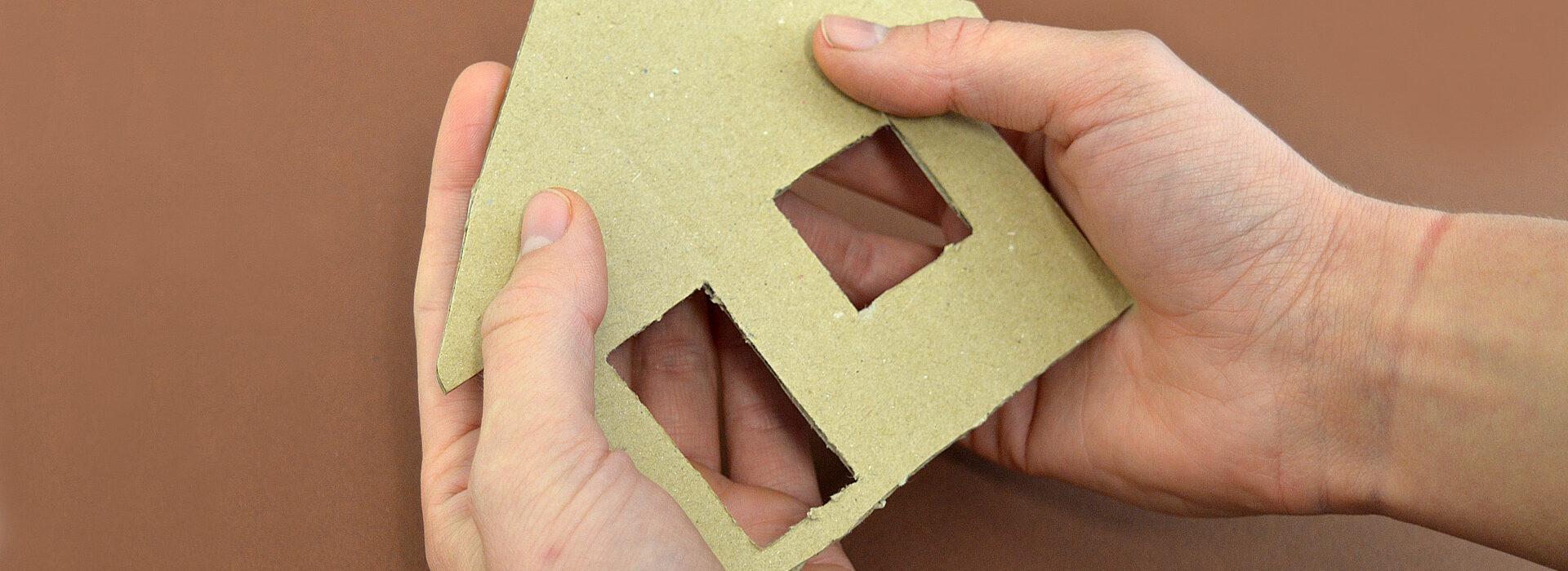 Foto: Wohnungsnot - Hände halten Haus aus Pappe