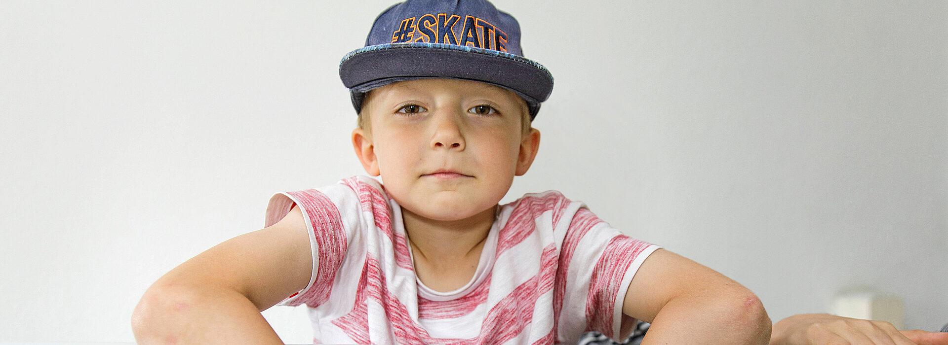 Foto: Kind mit Cap lehnt über Treppengeländer - Erziehungshilfen Diakonie Münster