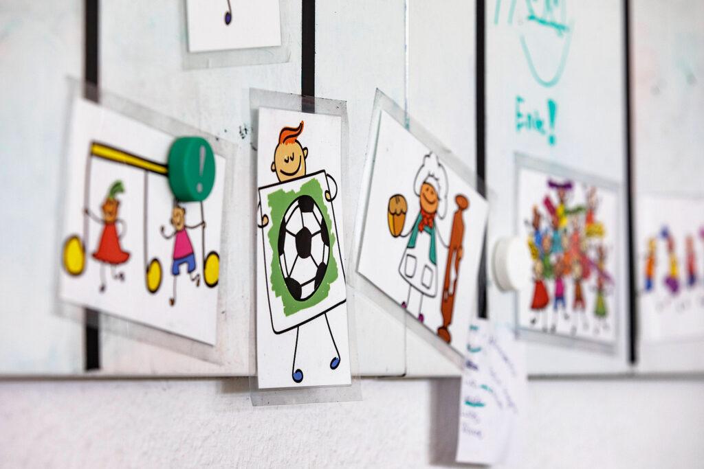 Foto: Pinwand mit lustigen Grafiken; HTGs der Diakonie Münster
