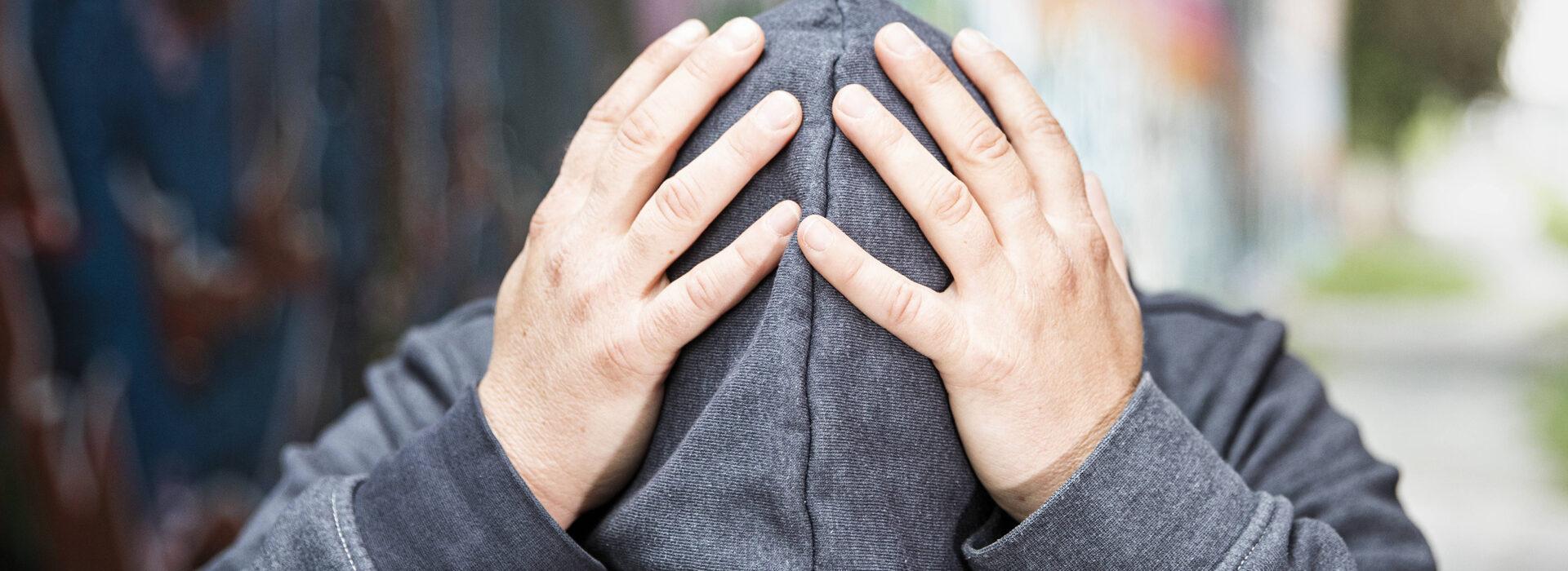 Foto: Hände halten den Kopf mit einer Kapuze- Inobhutnahme