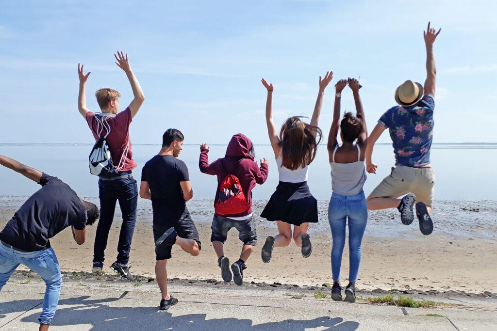 Foto: 7 Jugendliche stehen am Wasser und springen hoch