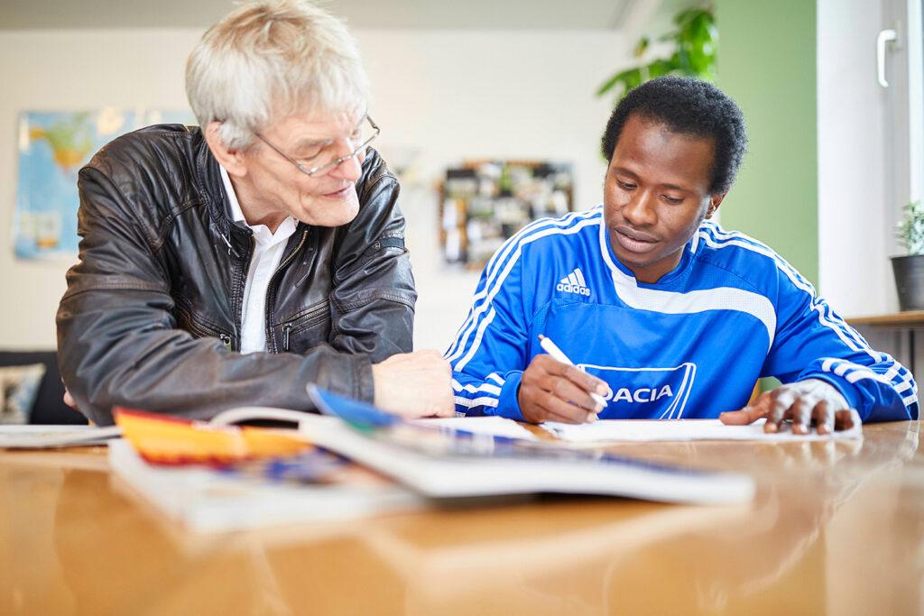 Foto: Älterer Mann hilft Jugendlichem bei den Hausaufgaben, Peter Umlauf, Ehrenamtler unterrichtet Jugendliche der Esperas Wohngruppe