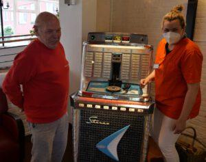 Bewohner und Pflegekraft vor der Jukebox