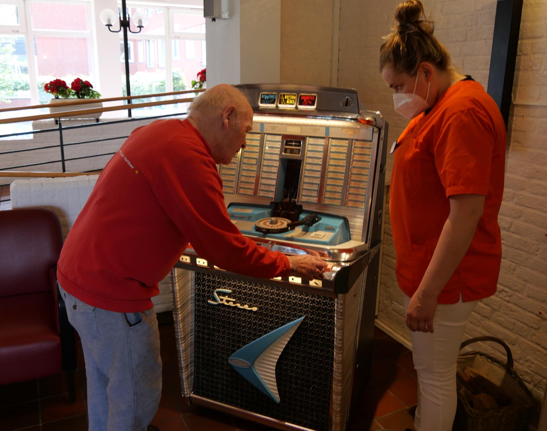 Foto: Ein Bewohner des MLH mit einer Pflegekraft bestaunen die Jukebox