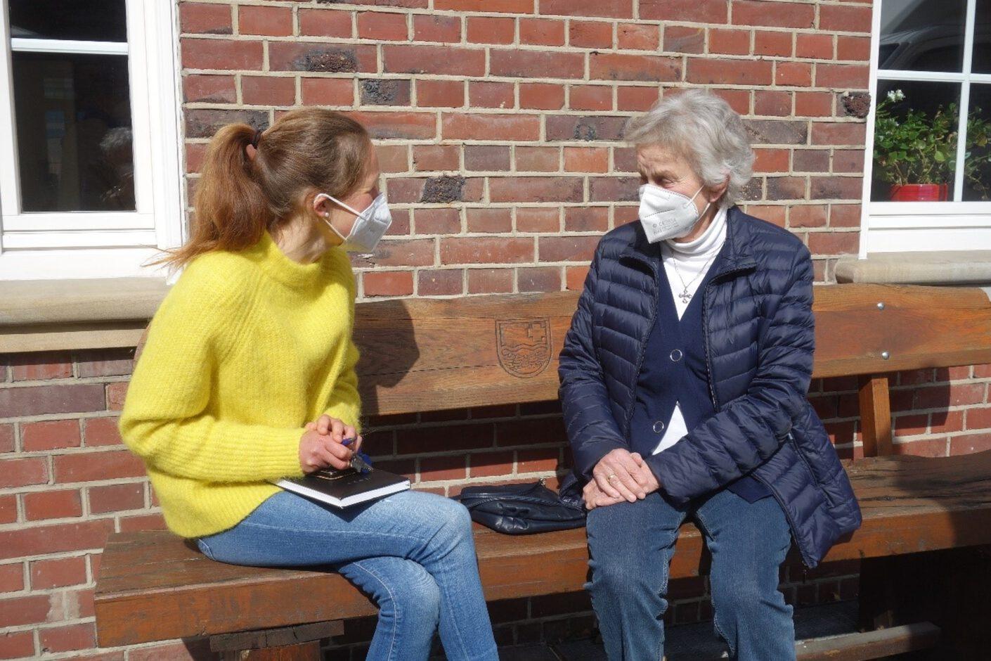 Foto: zwei Frauen sitzen auf der Plauderbank und unterhalten sich