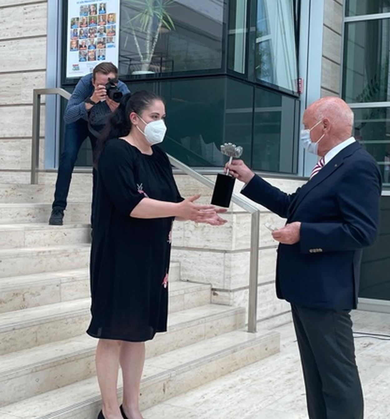 Foto: Architekt und Designer Dieter Sieger überreicht den Pflegepreis an eine Mitarbeiterin der Diakonie Münster