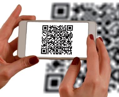 Foto: Hände halten ein Smartphone, auf dem ein QR Code zu sehen ist