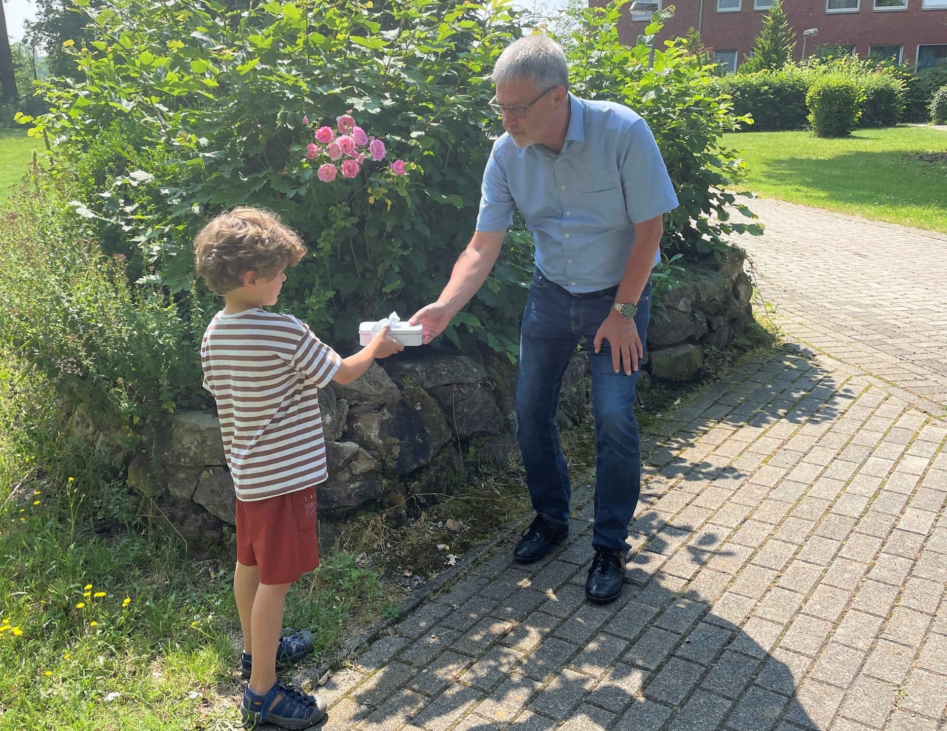 Foto: Junge überreicht Spende an Geschäftsführer der Jugendhilfe der Diakonie