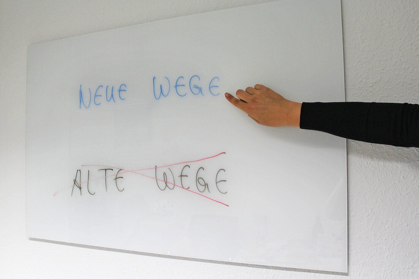 Foto: Whiteboard mit Text Neue Wege Alte Wege und einer richtungsweisenden Hand