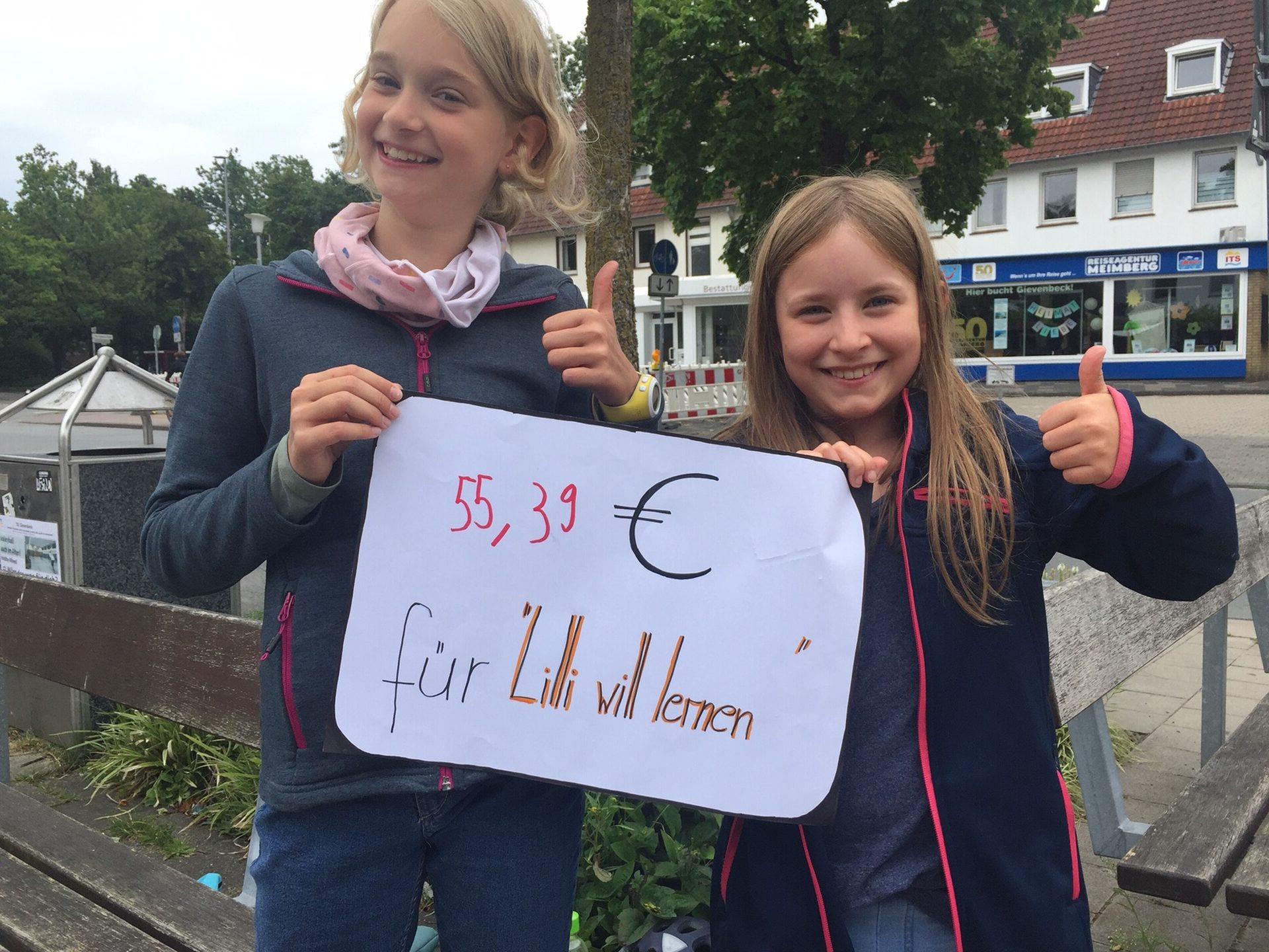 Foto: zwei Mädchen halten Schild mit Spendenerlös hoch