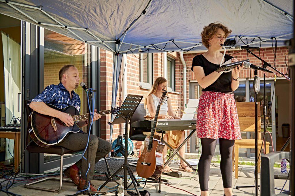 Foto: Ein Mann an einer Gitarre, eine Frau am Keyboard und eine Frau am Mikrophon mit Instrument