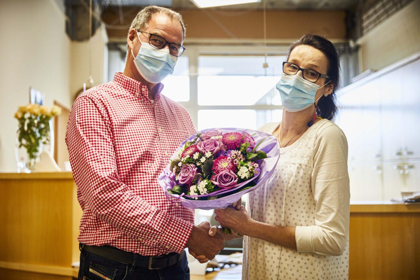 Foto: Einrichtungsleiter vom Haus Simeon gratuliert Mitarbeiterin mit Blumenstrauß